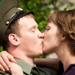 Girl kissing army boyfriend goodbye for awhile