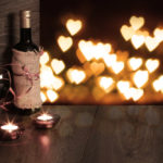 Romantic wine and candles with hearts in the air