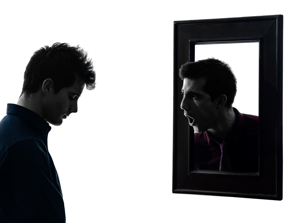 Man in front of his mirror in shadow
