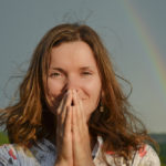 Grateful woman in front of rainbow