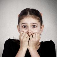 Fearful anxious girl biting nails